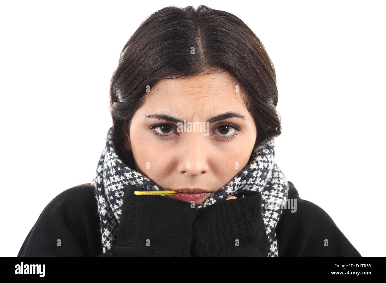 Very wrapped up ill girl with a thermometer on a white isolated background - Stock Image