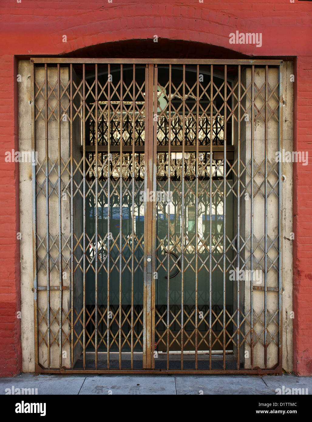 Old Steel Security Gate on door to red brick building Stock Photo