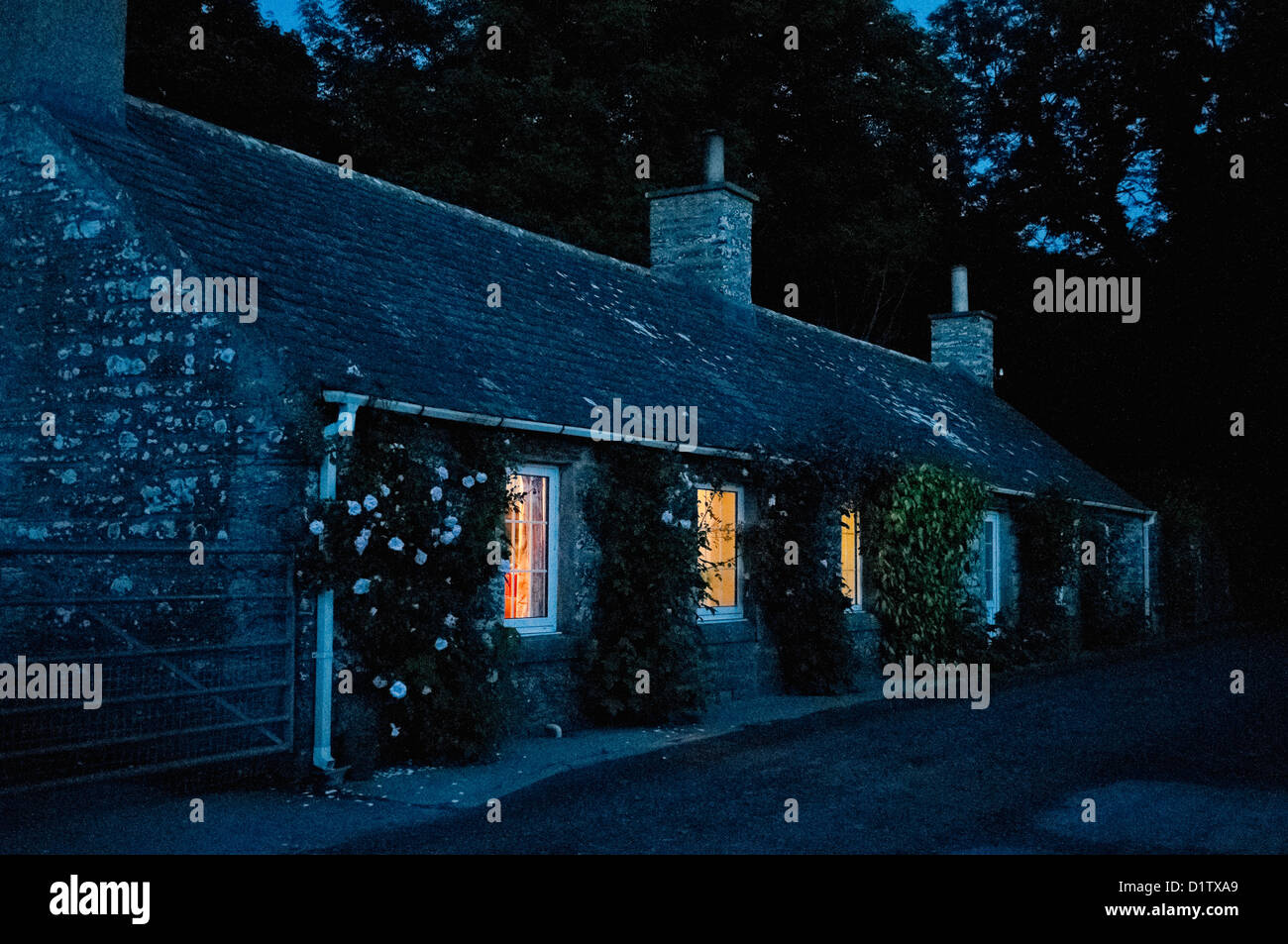 Old stone cottage at night, with light shining from windows. - Stock Image