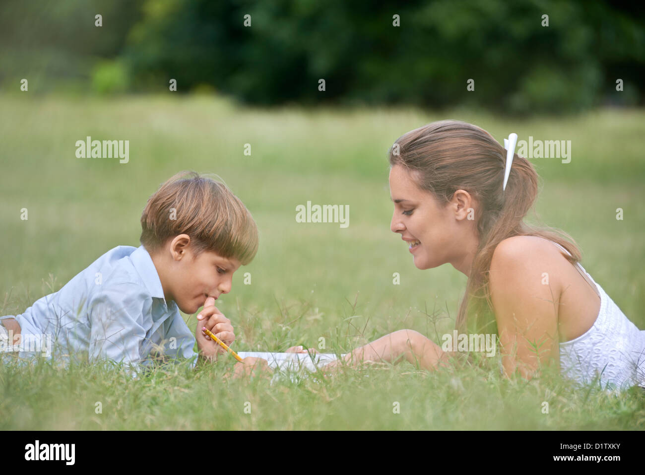 People and education, mother helping child with homework, lying on grass and reading book at park. Medium shot - Stock Image