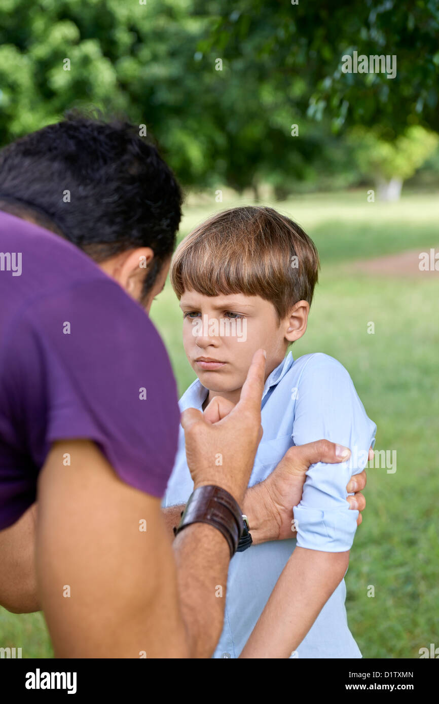 Young people and difficult parenthood, upset father scolding scared son while holding his arm. Waist up, focus on - Stock Image