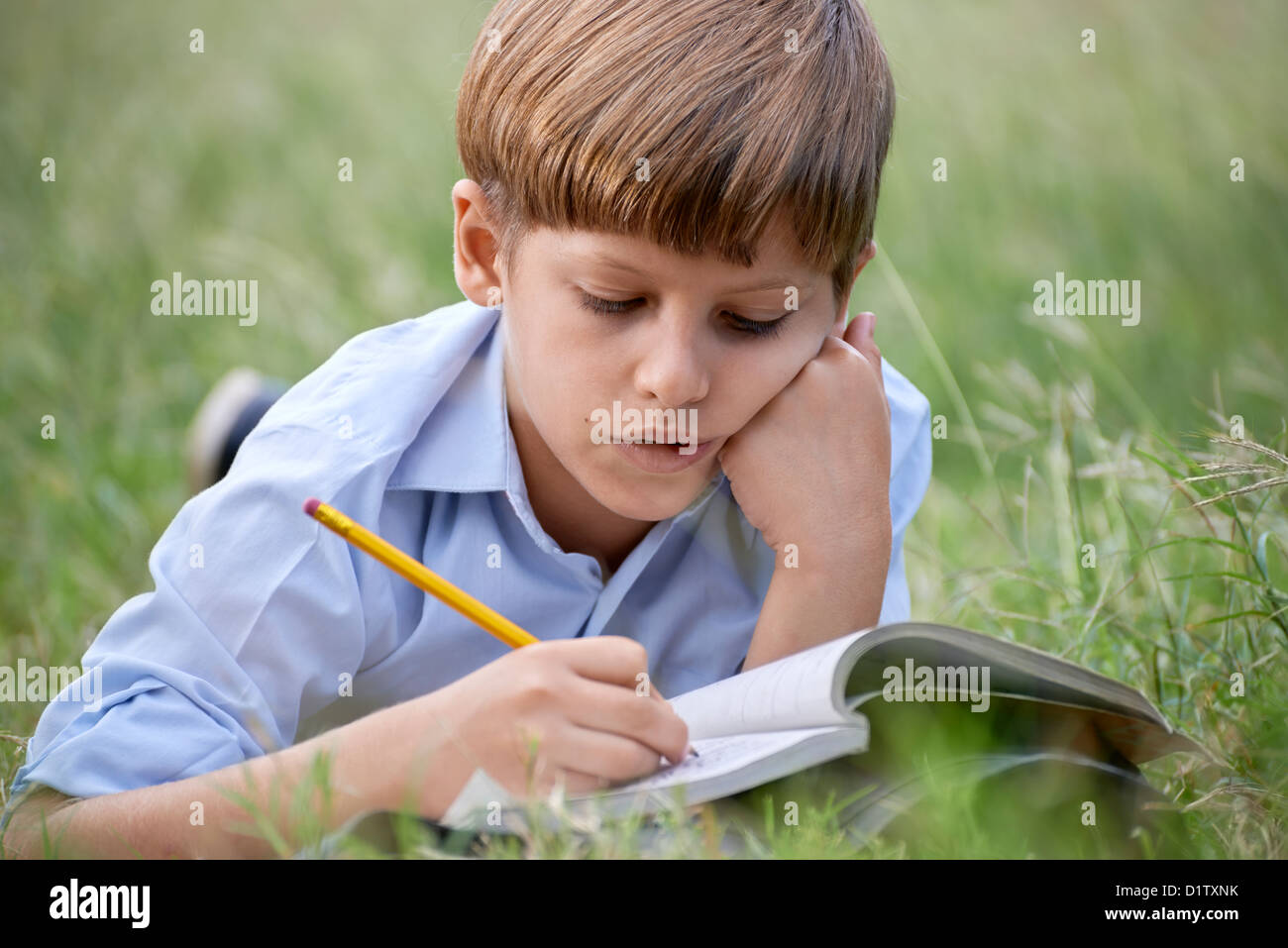 Young people and education, school child doing homework, laying down on grass at park and studying with book. Medium - Stock Image