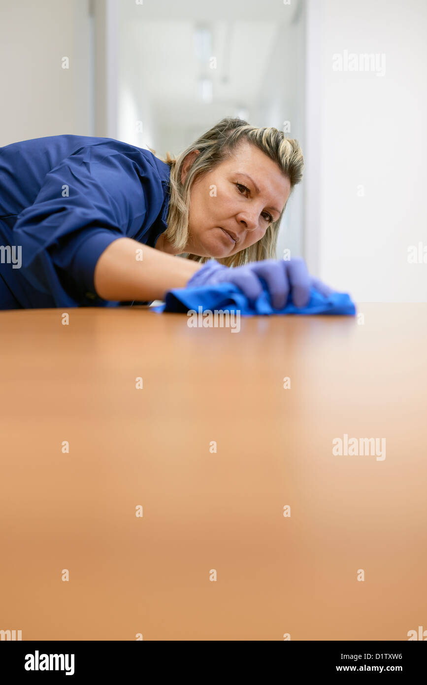 Woman at work, professional maid cleaning desk in office. Copy space - Stock Image