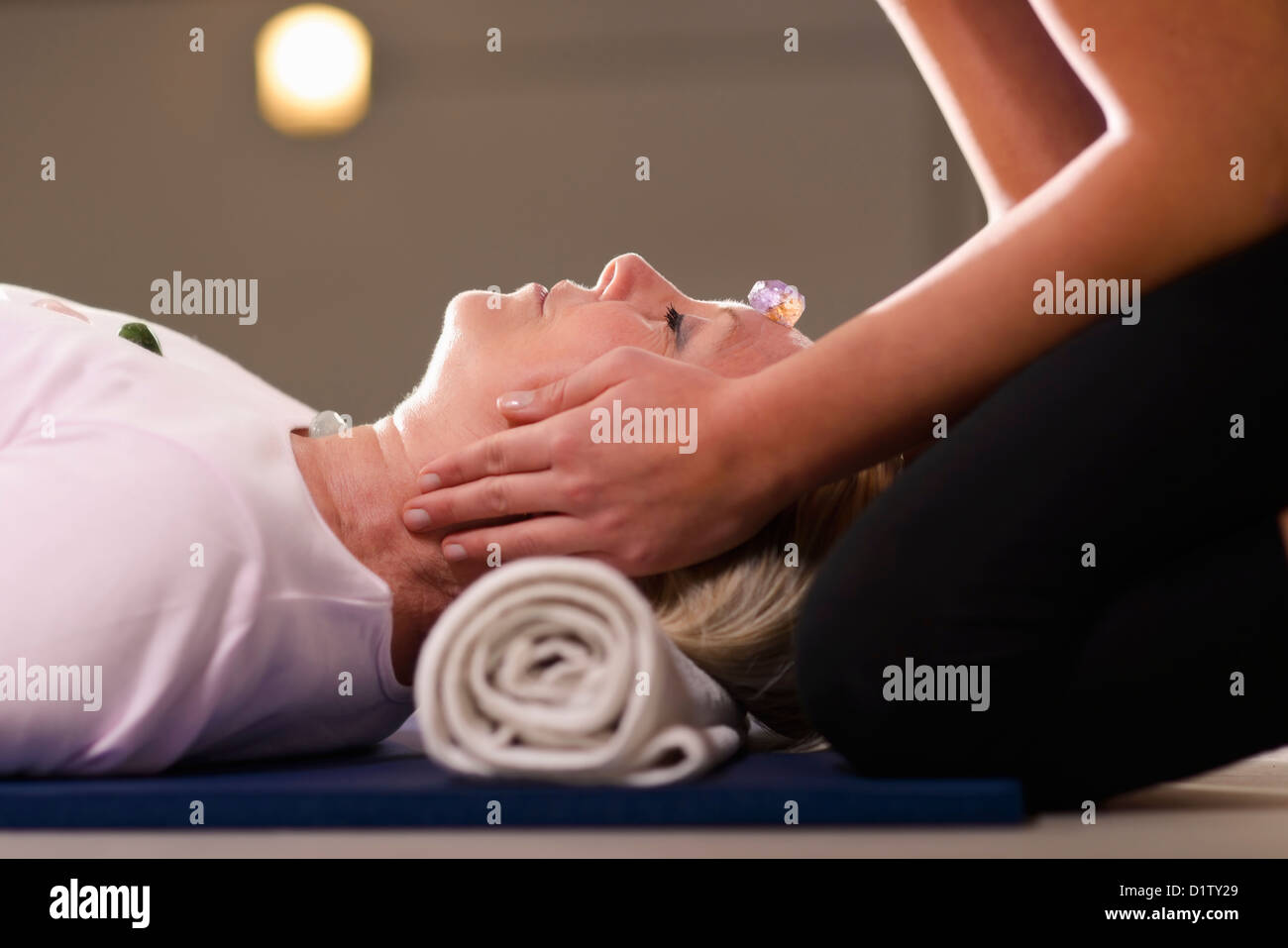 Reiki therapy with girl working as spirit healer, arranging crystals and gemstones on female client for treatment - Stock Image