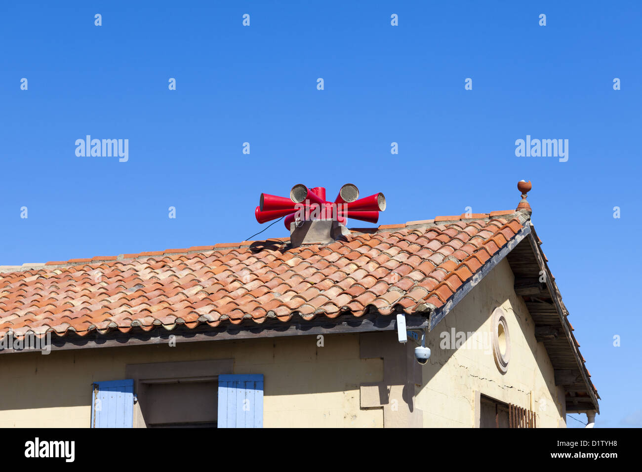 Big red fire siren on house roof against a blue sky - Stock Image