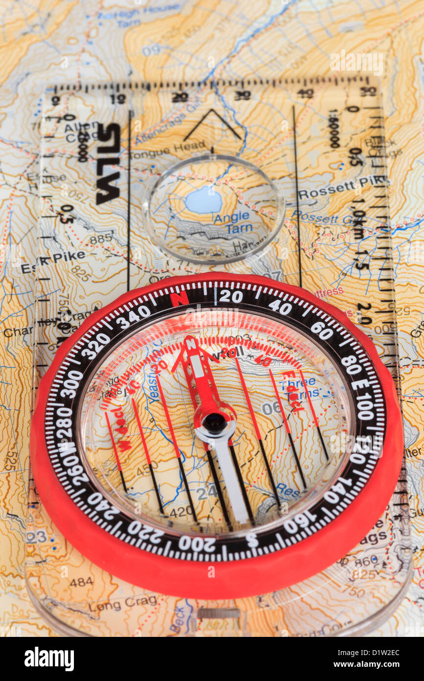 Orienteering compass needle pointing north with grid lines on a Harvey's 1:40000 hiking map and baseplate arrow - Stock Image