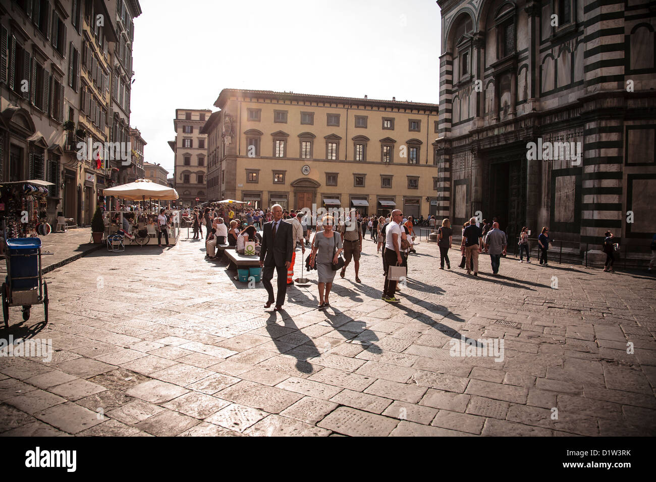Tourists and locals wander through the Piazza del Duomo in Florence on a lovely summer evening. - Stock Image