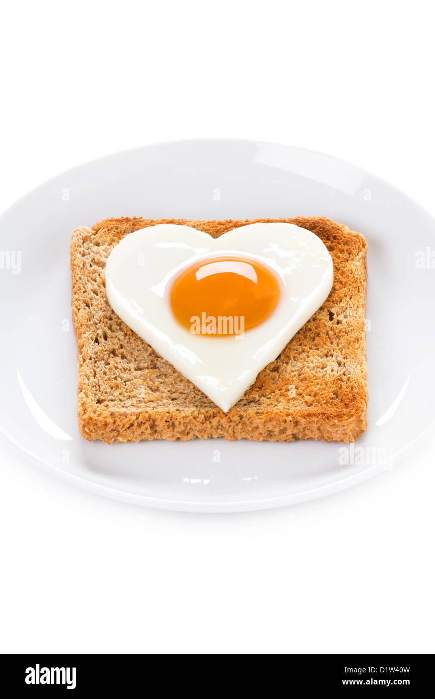 heart shaped cooked egg on toast to illustrate valentines day breakfast or cholesterol health message Stock Photo