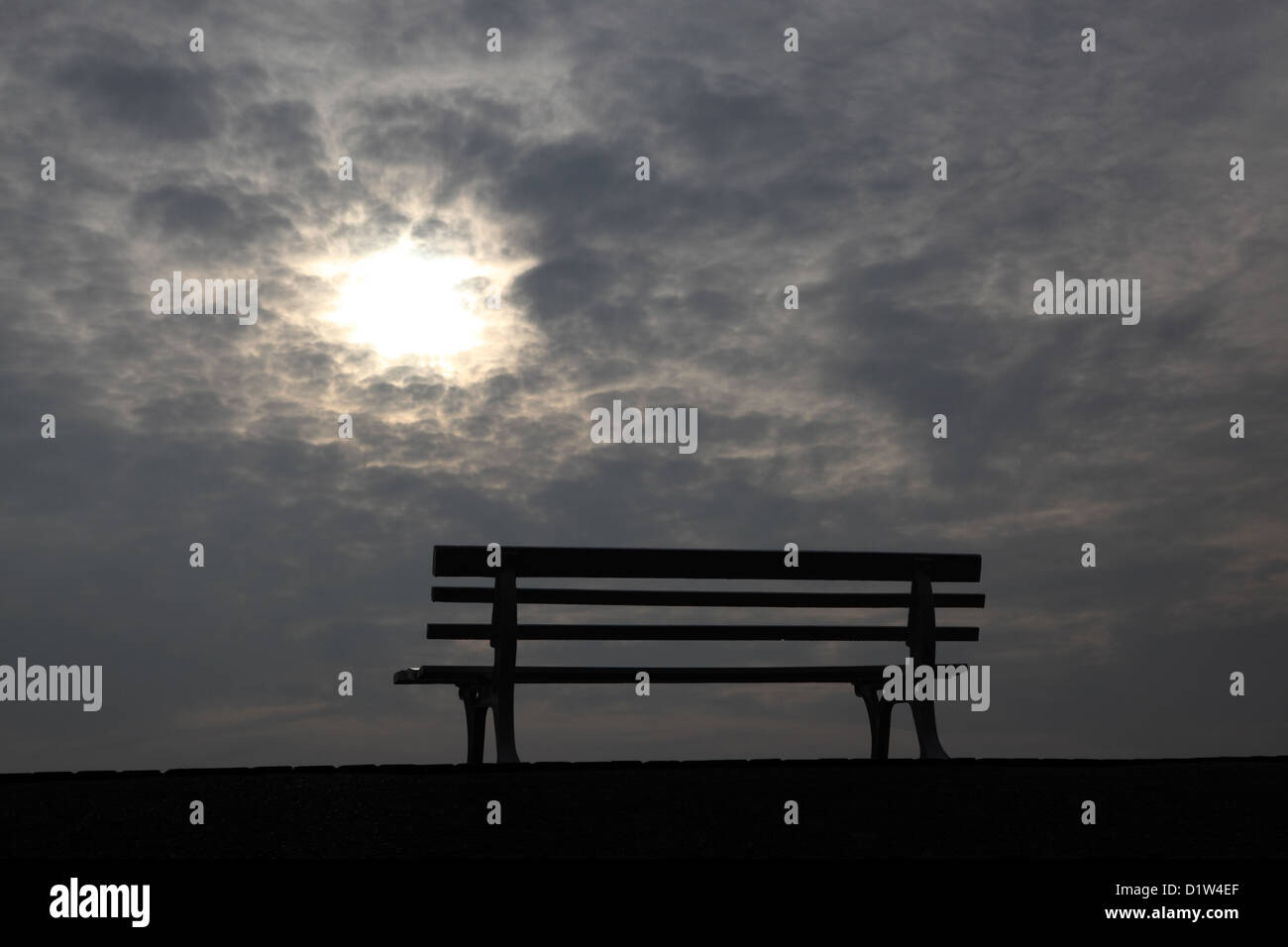 Hanover, silhouette, empty park bench in front of cloudy sky Stock Photo