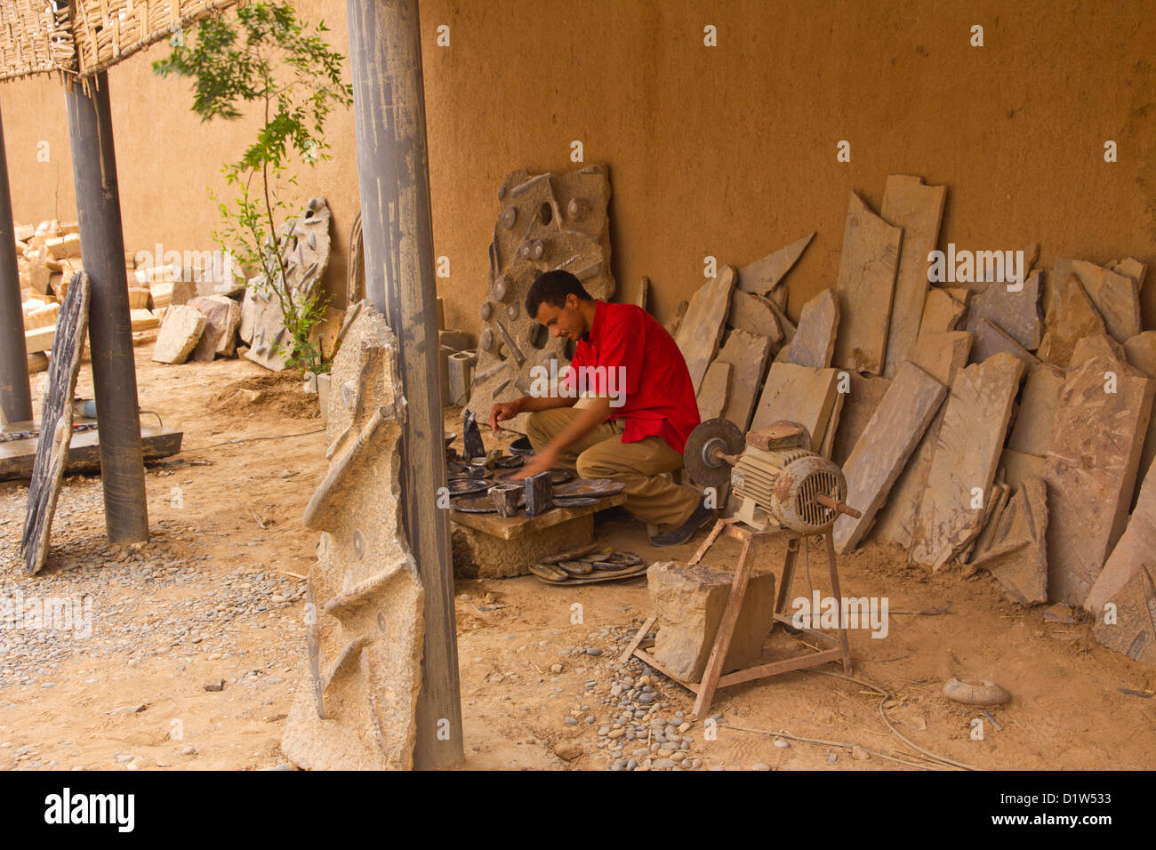 Man sitting polishing and preparing fossils. Stock Photo