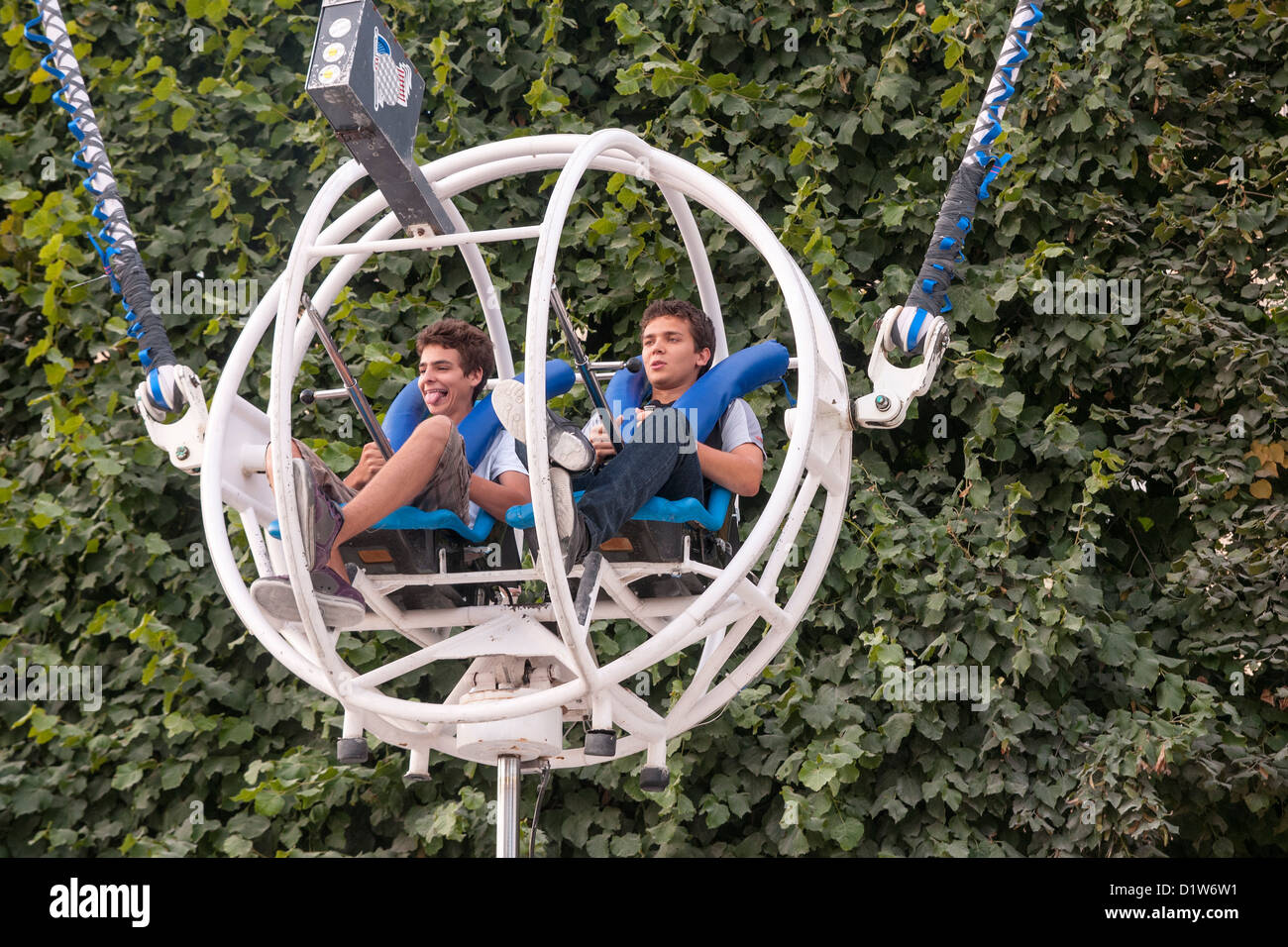 Two teenage boys in a inverted Bungee steel cage ball, reverse ejection seating View from the front. Close up - Stock Image