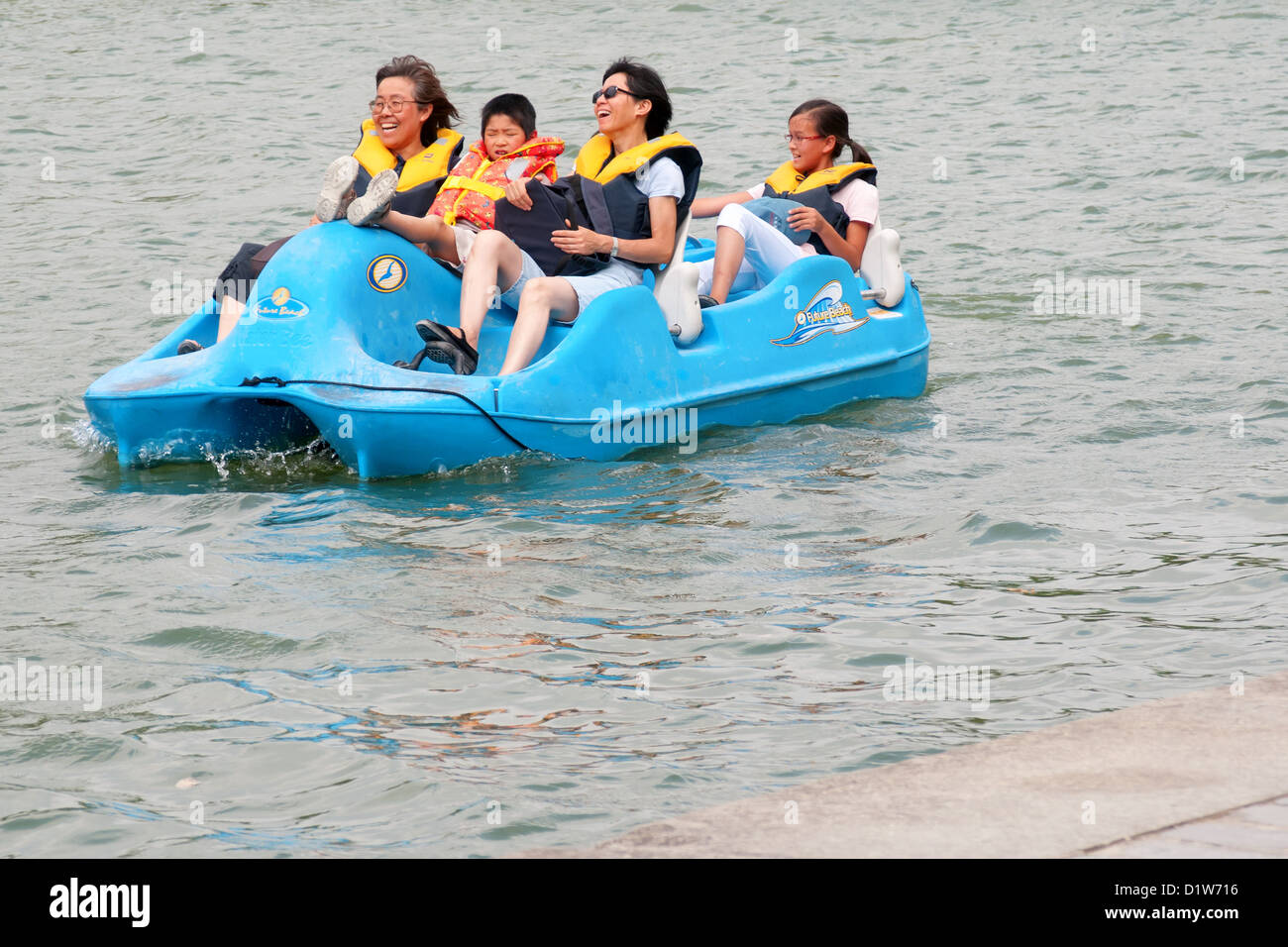 Messing about on the water, Paddle boat trip by some tourists having fun on a cold day - Stock Image