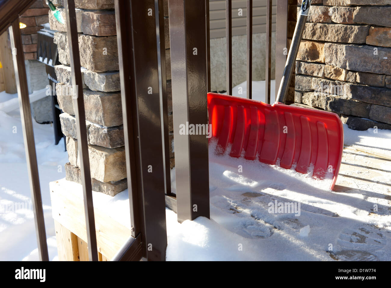 snow shovel on the porch of a suburban house in Saskatoon Saskatchewan Canada - Stock Image