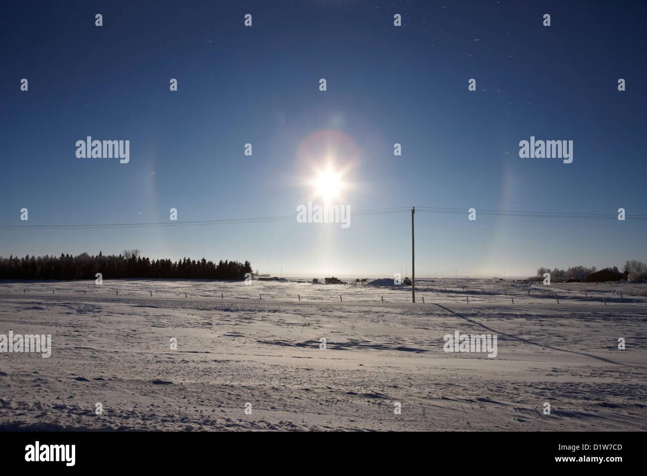 pair of sun dog parhelion halo due to ice crystals surrounding the sun in Saskatchewan Canada - Stock Image