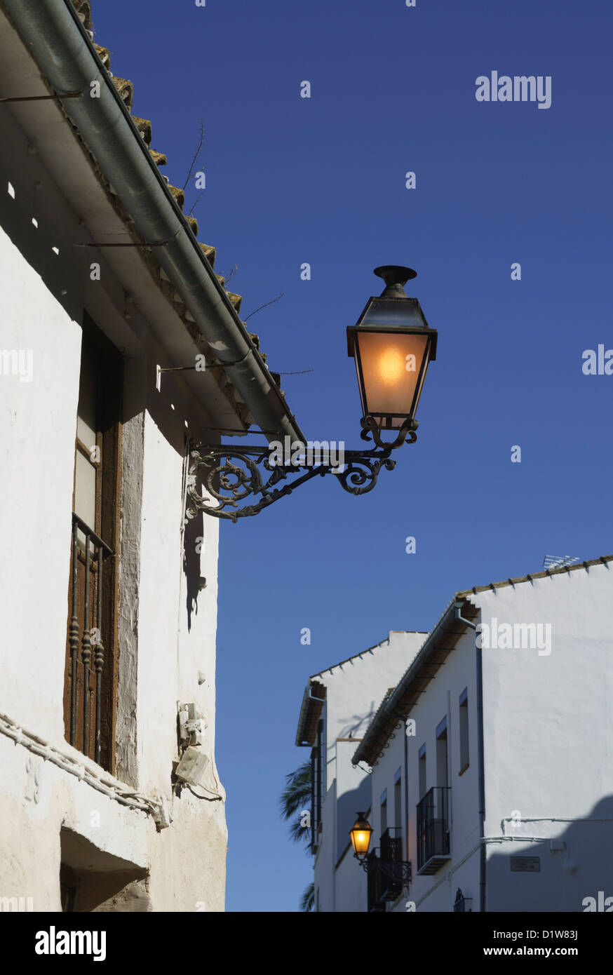 Spain, Andalucia - Antequera. A street light burns in bright daylight. - Stock Image