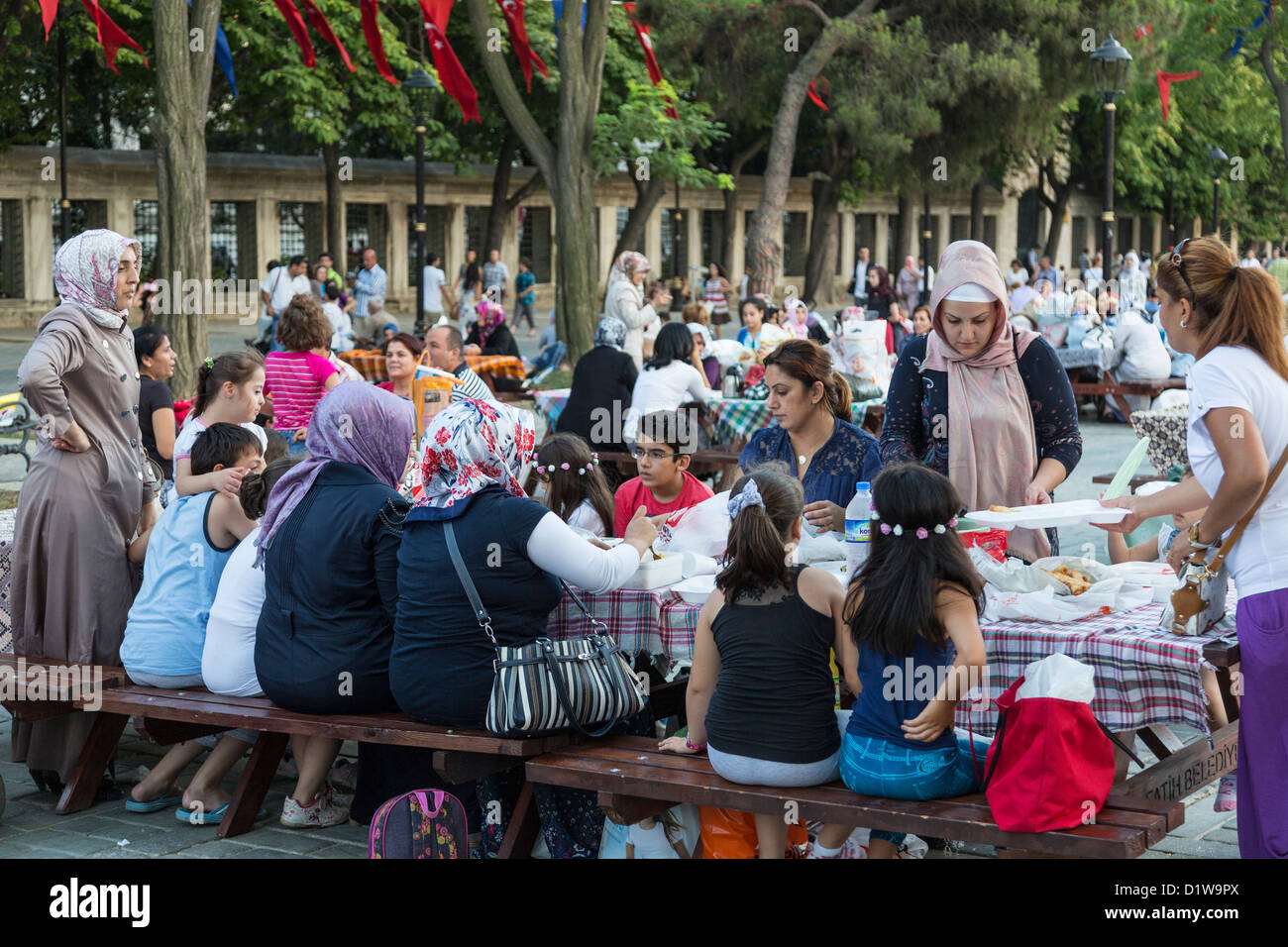 Muslim women awaiting sunset at Ramadan, Sultan Ahmet Square Istanbul, Turkey - Stock Image