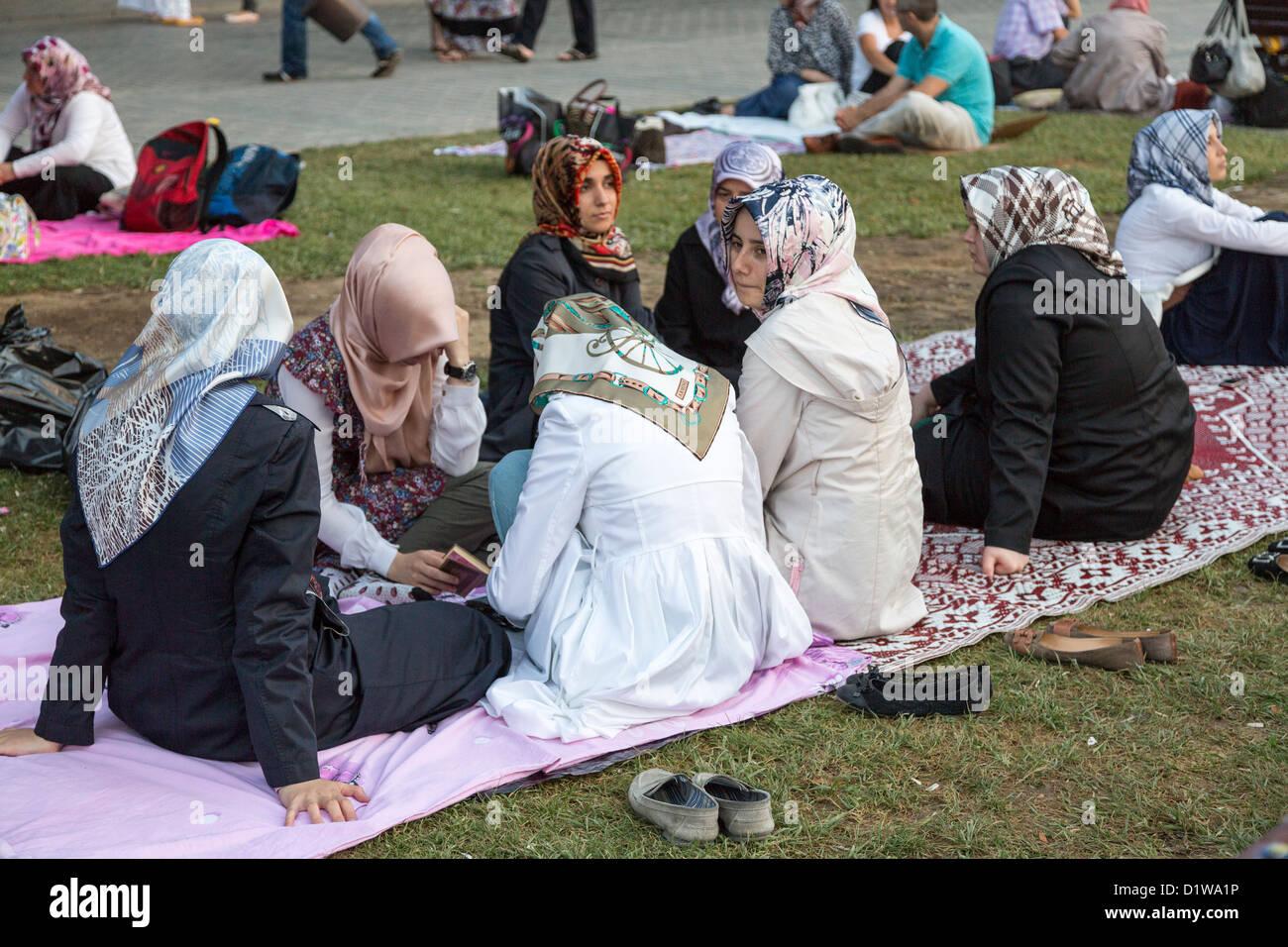 Muslim women awaiting sunset at Ramadan, Sultan Ahmet Square Istanbul, Turkey - Stock Image