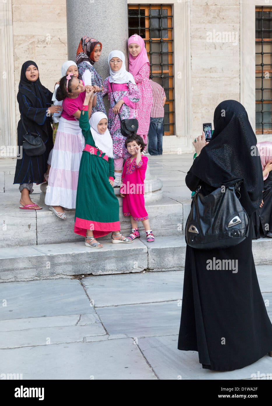 Muslim family posing for photograph, Sultan Ahmet Mosque, Istanbul, Turkey - Stock Image