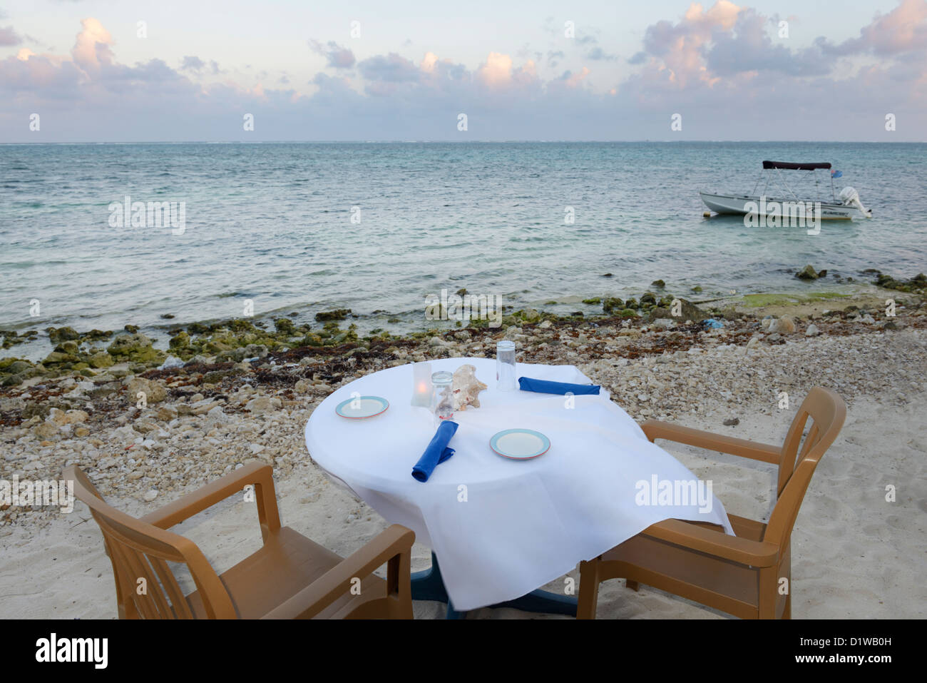 Restaurant table on beach at sunset over the Caribbean, East End of Grand Cayman. - Stock Image