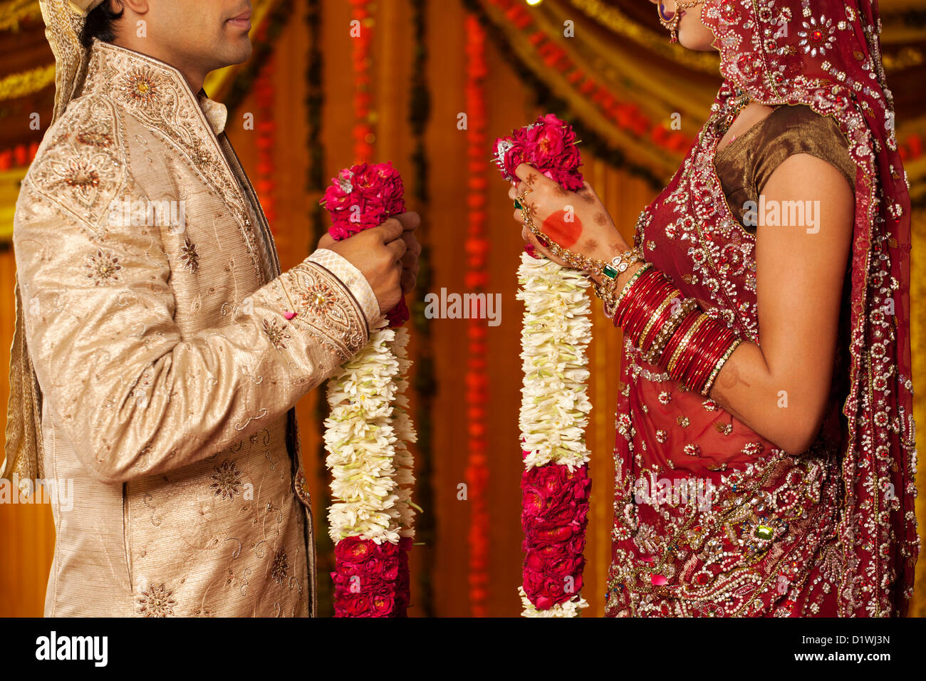 Indian bride and groom holding garlands - Stock Image