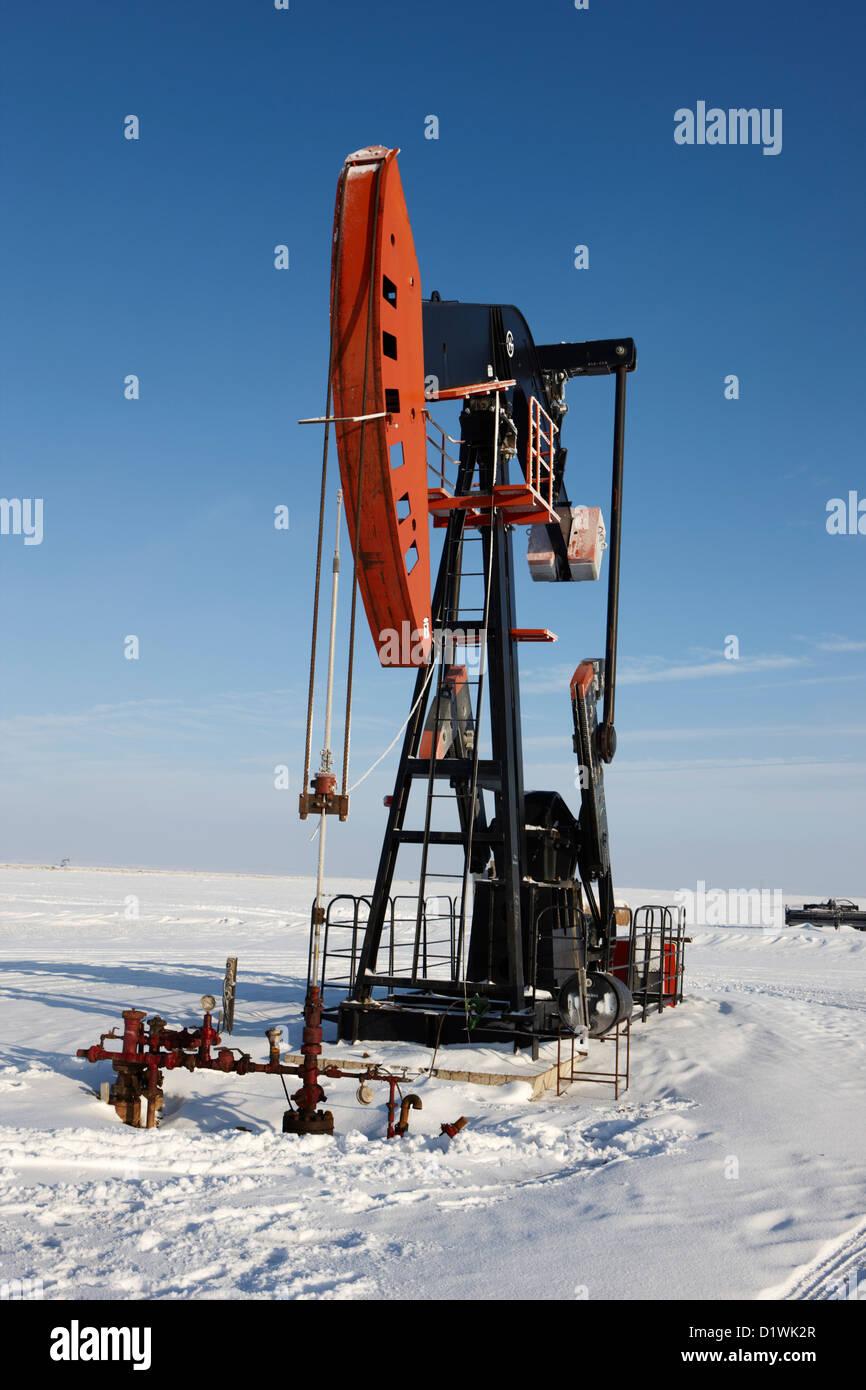 oil pumpjack in winter snow Forget Saskatchewan Canada - Stock Image