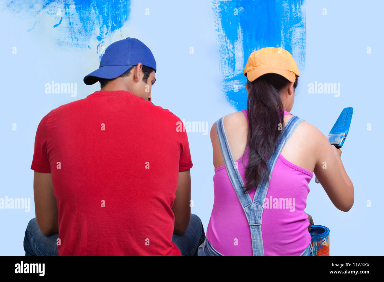 Rear view of young couple sitting with incomplete painted wall - Stock Image