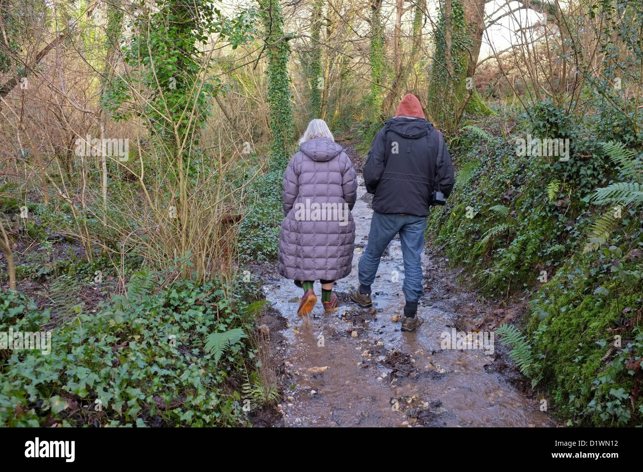 Mother and her grown-up son walking along a muddy path in Cornwall, UK - Stock Image