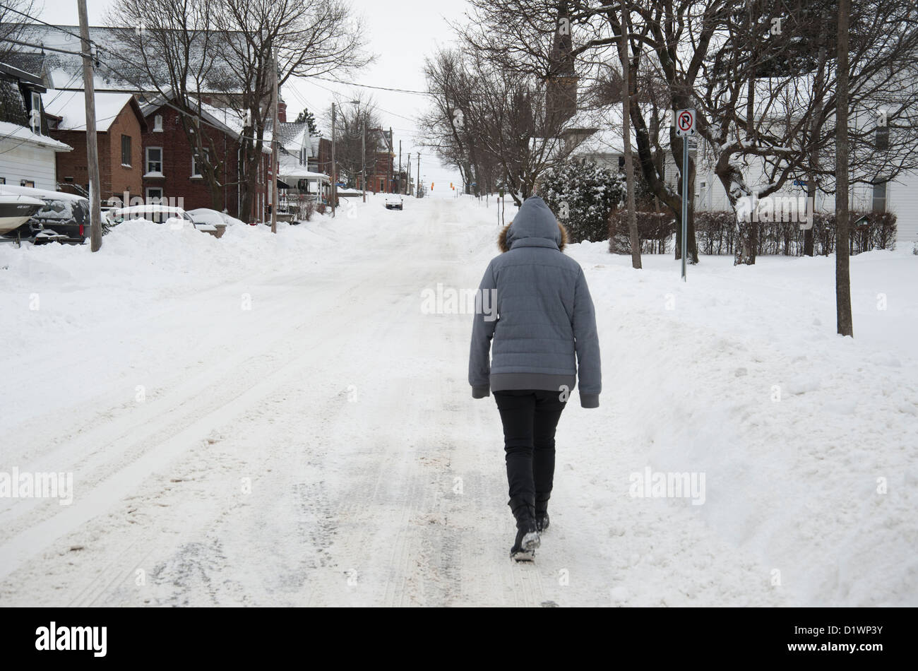 Woman walking down a snowy street in small town Canada in winter - Stock Image