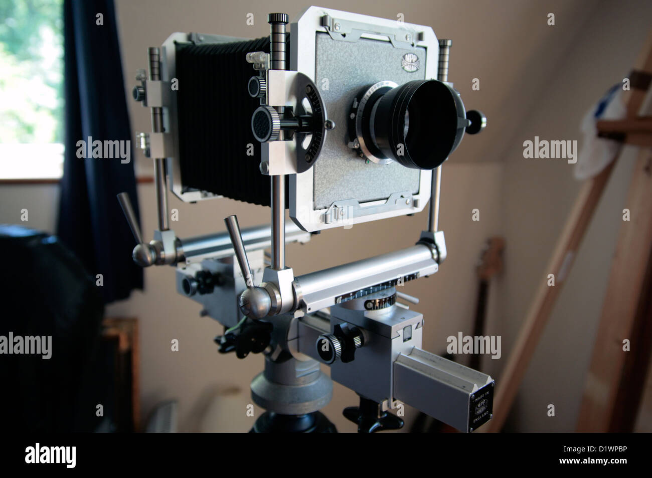 A large format film camera on a wooden tripod. - Stock Image