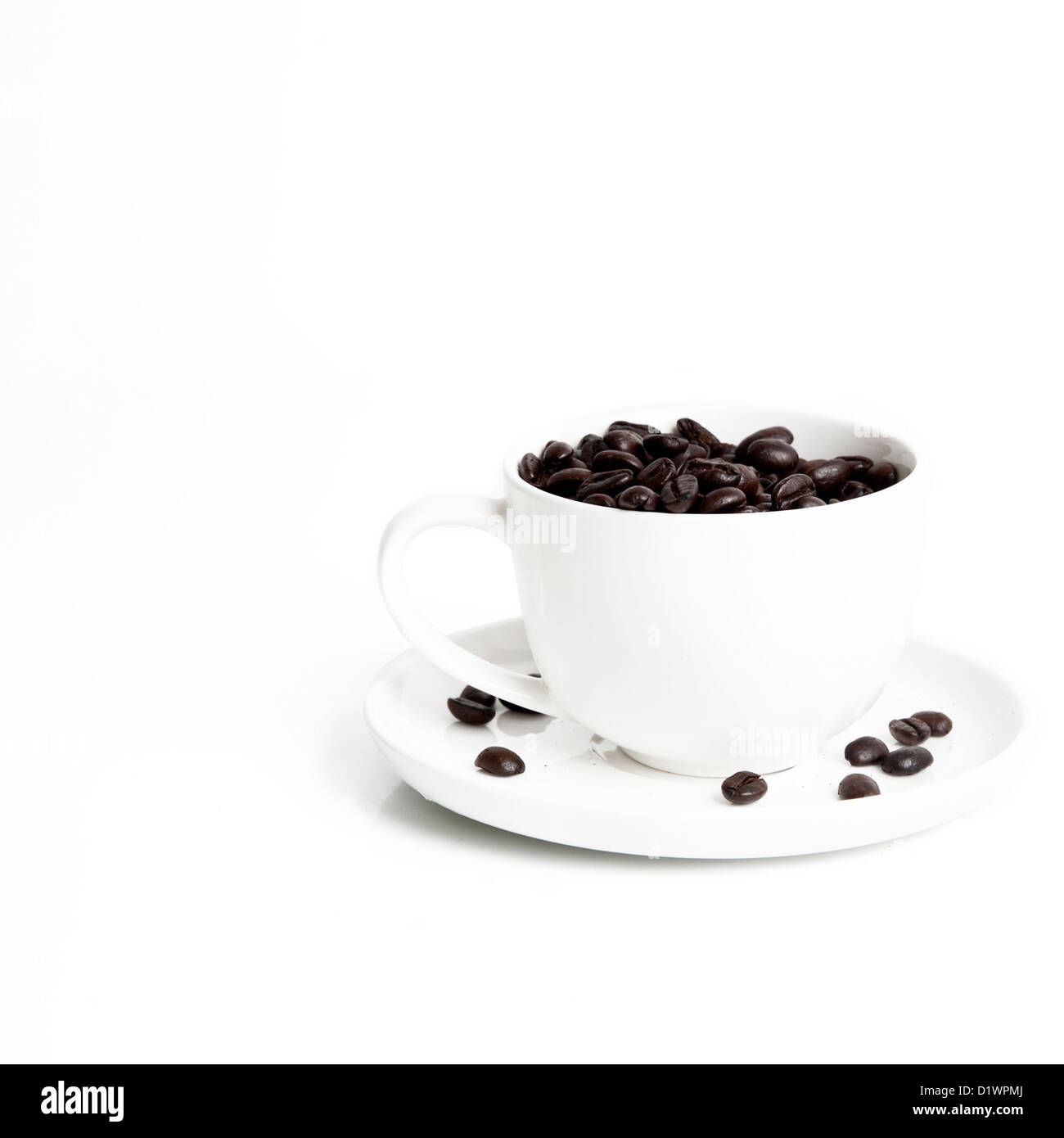 Coffee cup and saucer filled with coffee beans - Stock Image