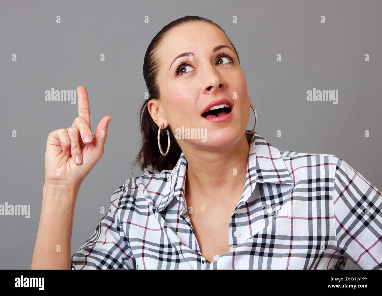 Woman with her finger in the air, having a great idea - Stock Image
