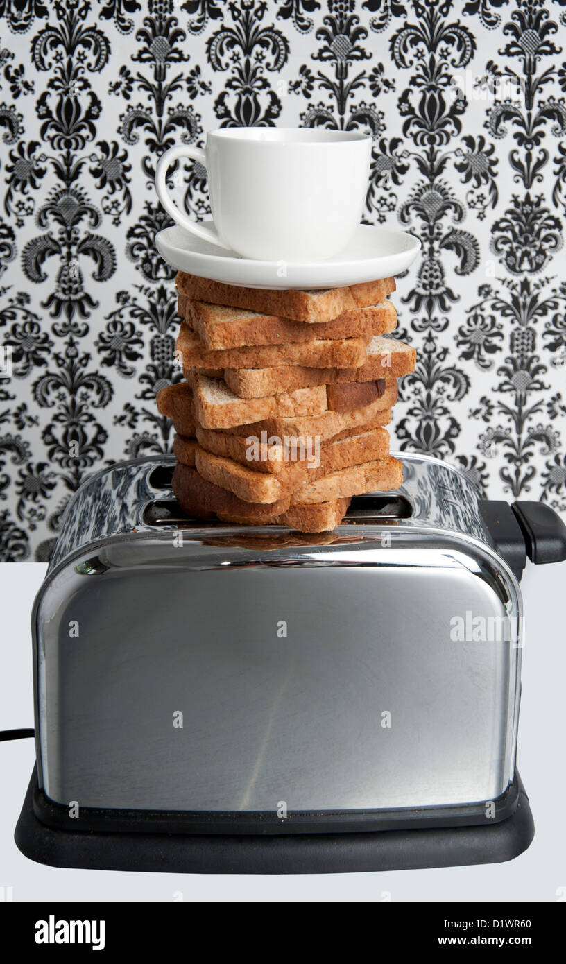 Toast and coffee balanced on top of a toaster - Stock Image
