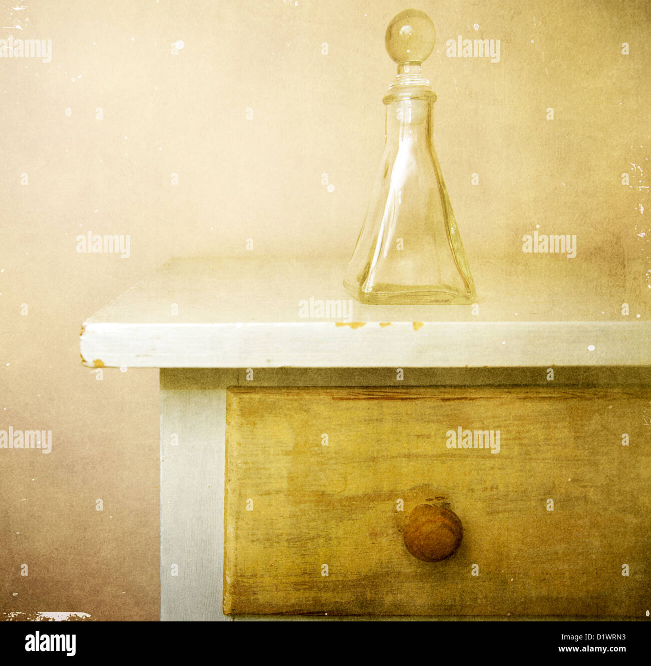 Glass perfume bottle is sitting on top of a bureau in a bedroom - Stock Image