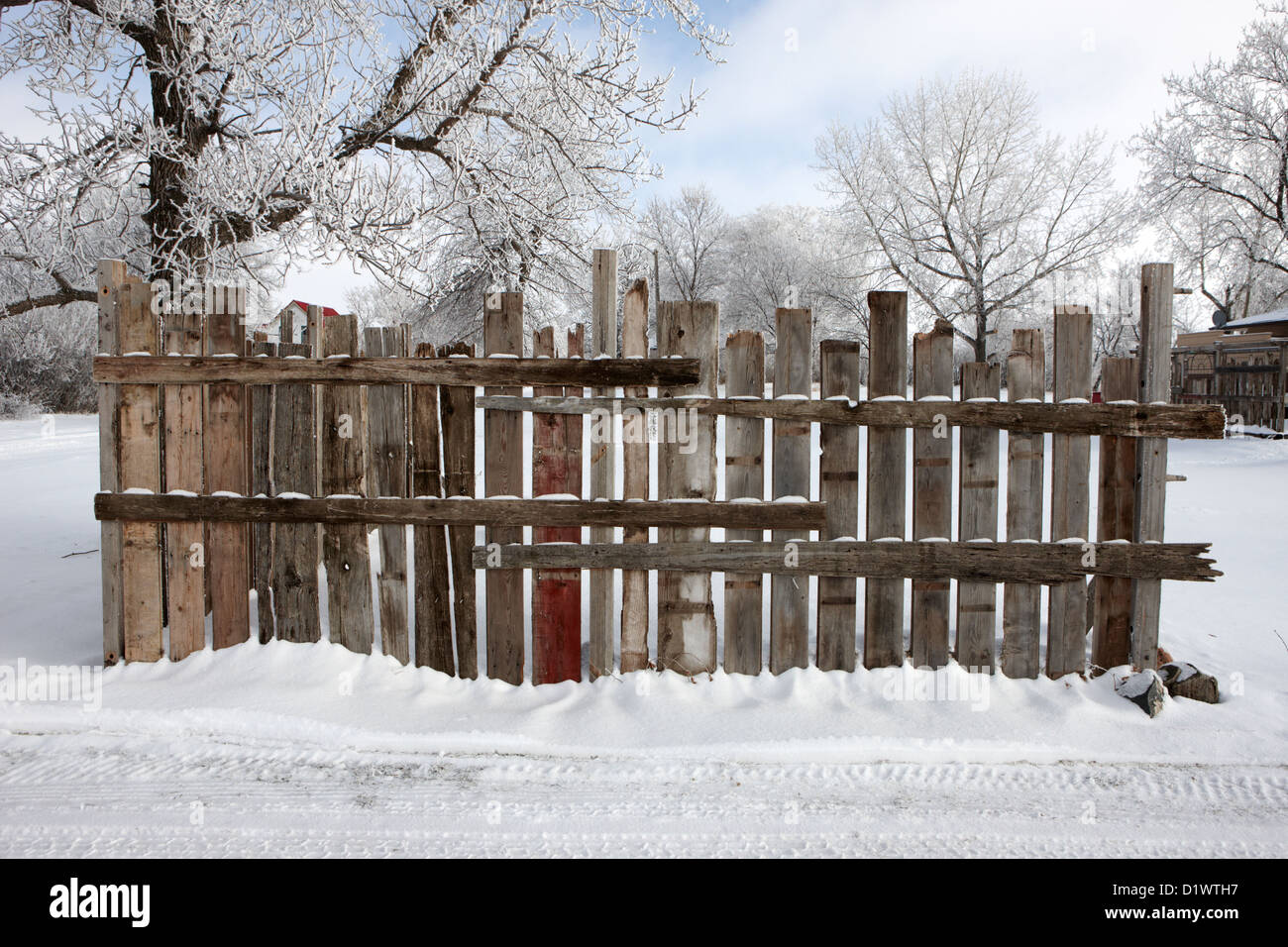 old patched up wooden fence using old bits of wood in snow Forget Saskatchewan Canada - Stock Image