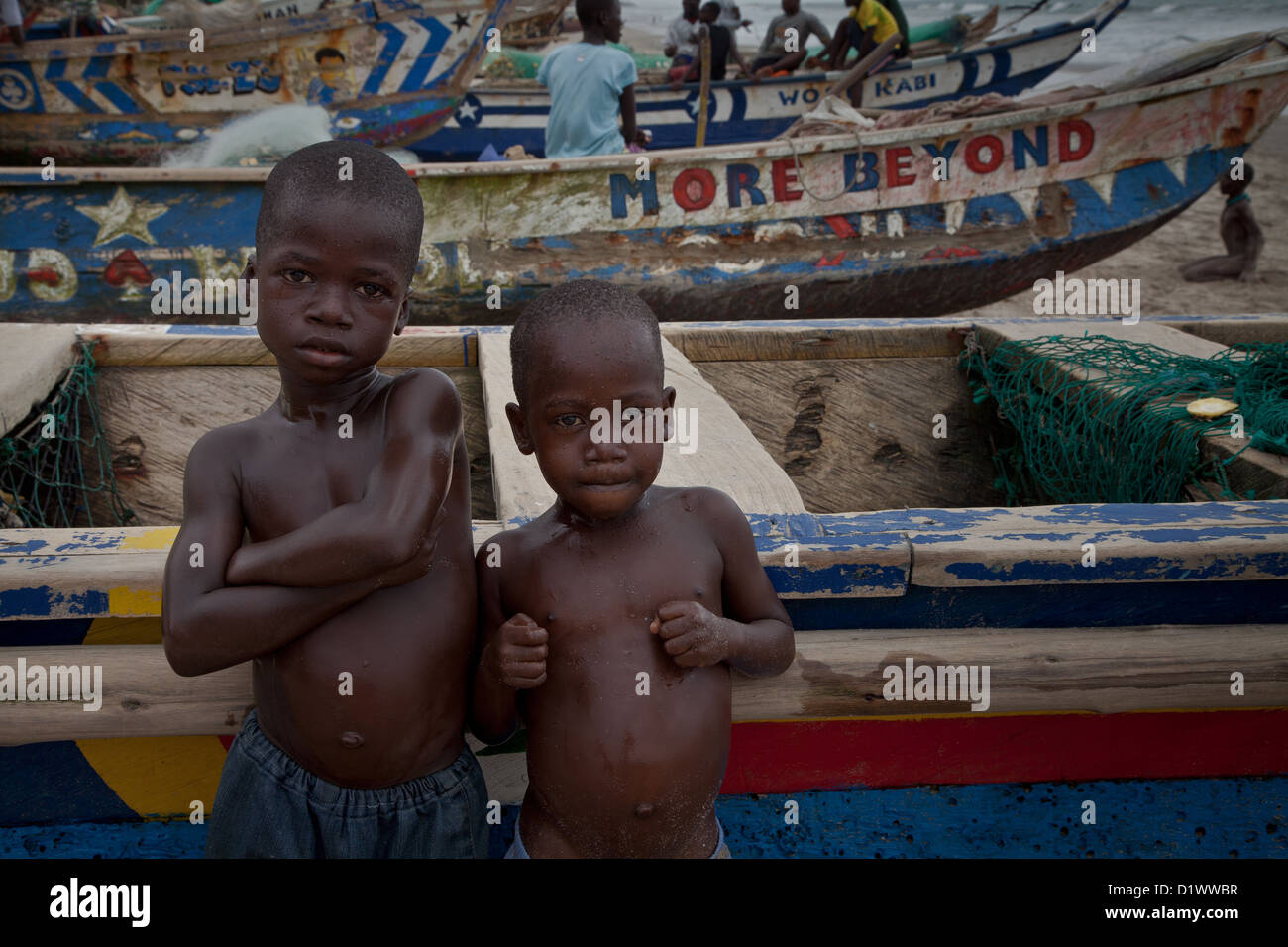 Two young boys look towards cameralean against a wooden fishing boat on a beach in Ghana. - Stock Image