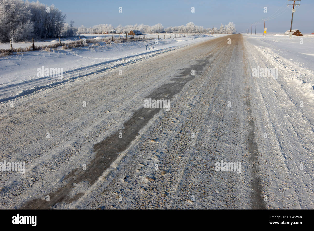 frozen salt and grit covered rural small road in Forget Saskatchewan Canada - Stock Image