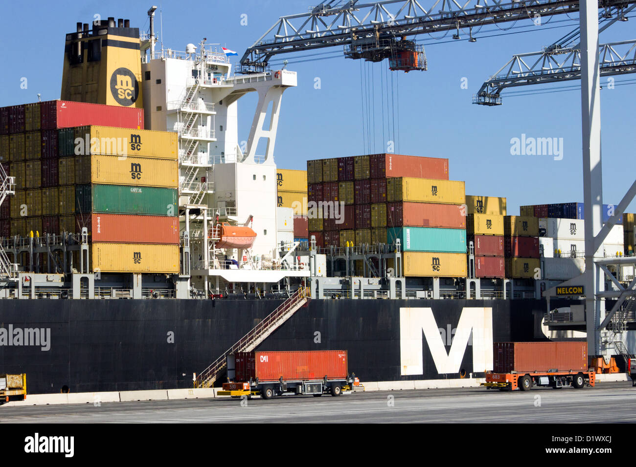 Container ship being loaded at Rotterdam sea port. Stock Photo