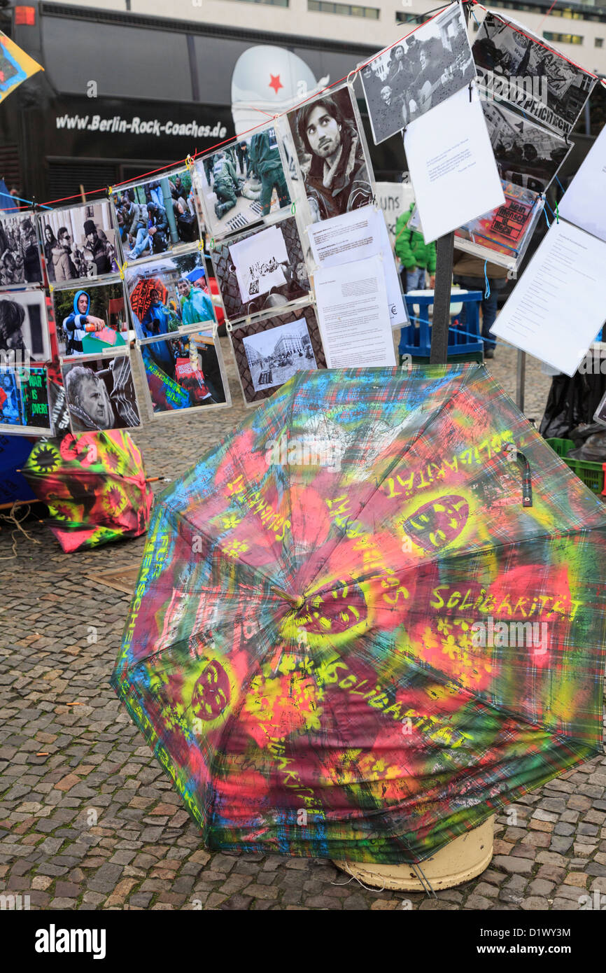 Protest in support of Iranian asylum seekers with colourful umbrella photographs and information in Pariser Platz - Stock Image