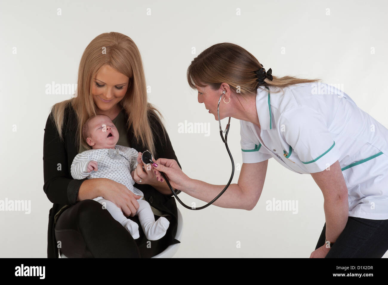 new mother holding her baby girl during postnatal medical examination with a nurse stock image