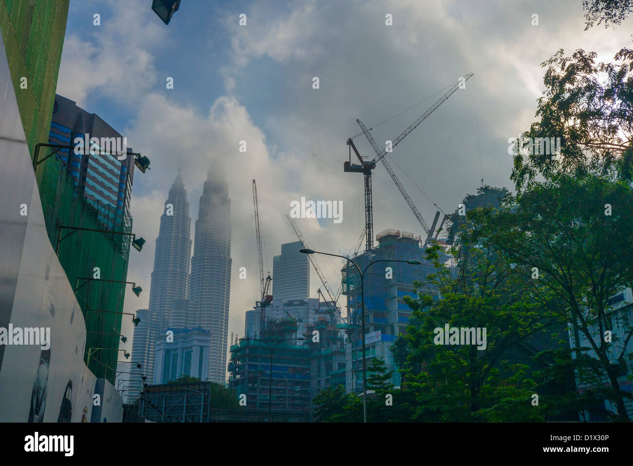 Clouds scraping the top of the Petronas twin towers with construction work underway in the foreground - Stock Image