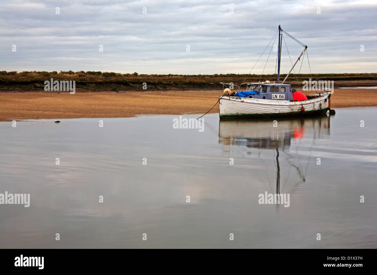 An inshore fishing boat with reflection anchored at Burnham Overy Staithe, Norfolk, England, United Kingdom. - Stock Image