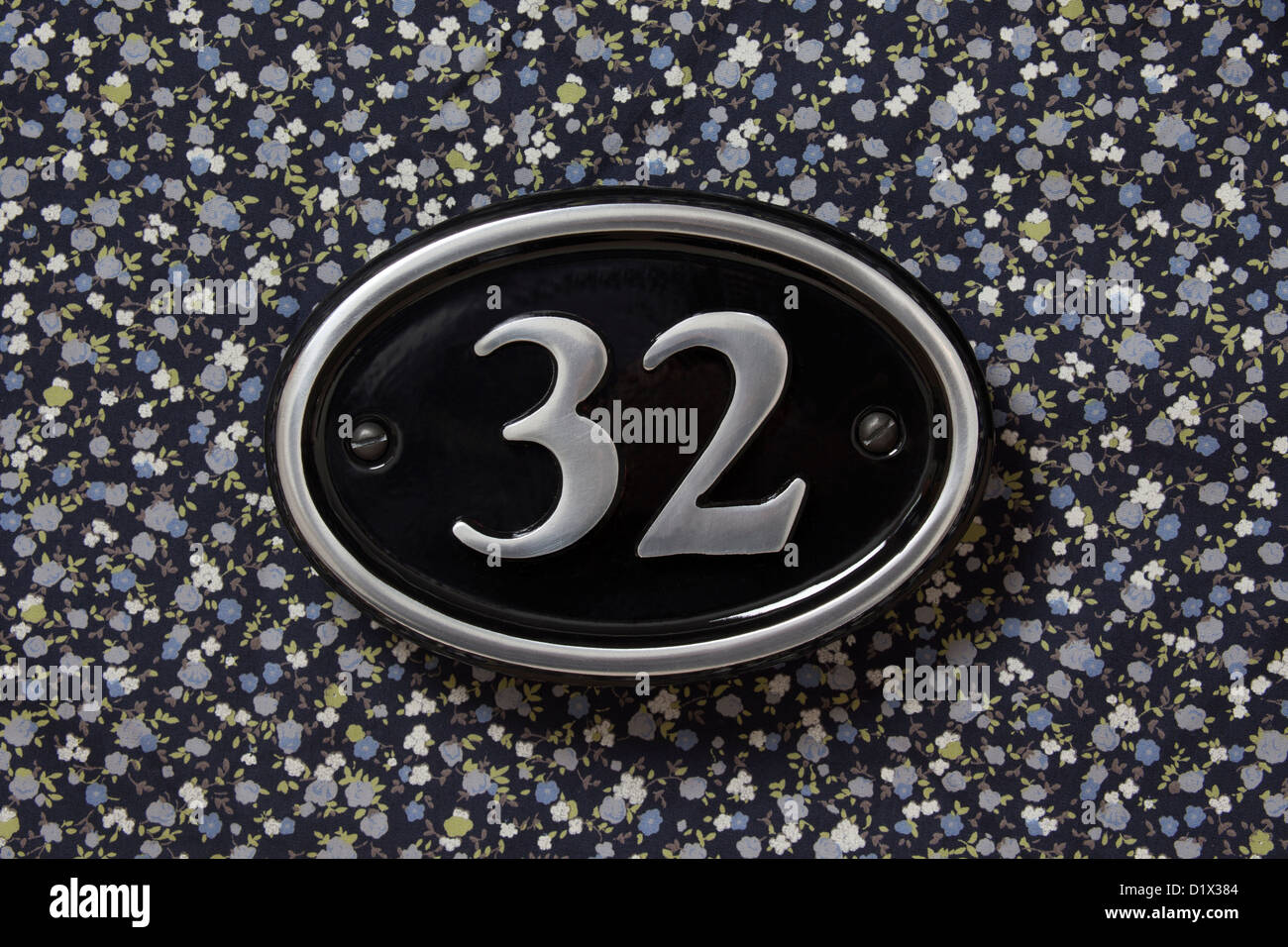 Number 32 metal silver and black house sign on a floral background. Stock Photo