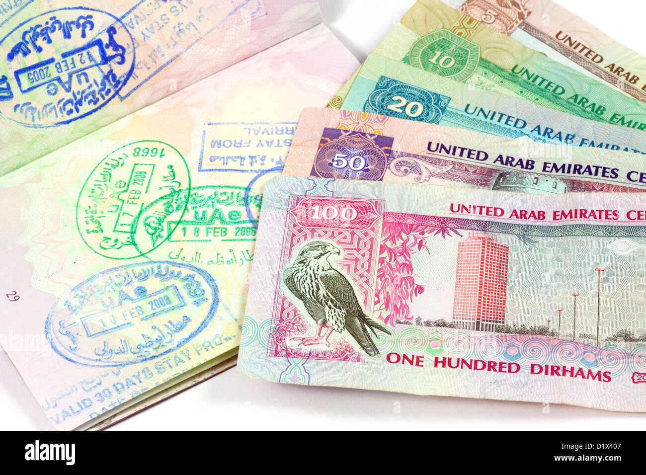 UAE holiday travel money currency and visa stamps in a passport for Dubai and Abu Dhabi - Stock Image