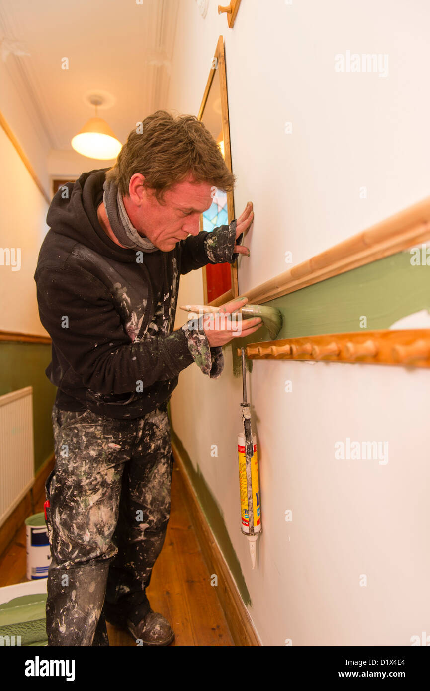 A self employed freelance painter and decorator painting the hallway wall of a house UK - Stock Image