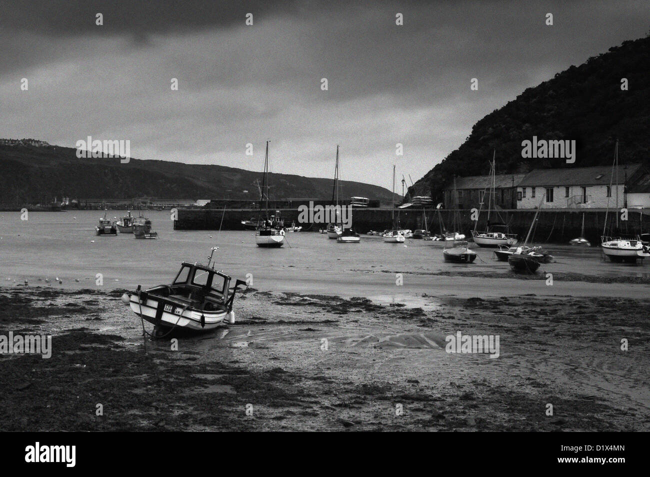 low tide at lower fishguard harbour on a rainy day. - Stock Image