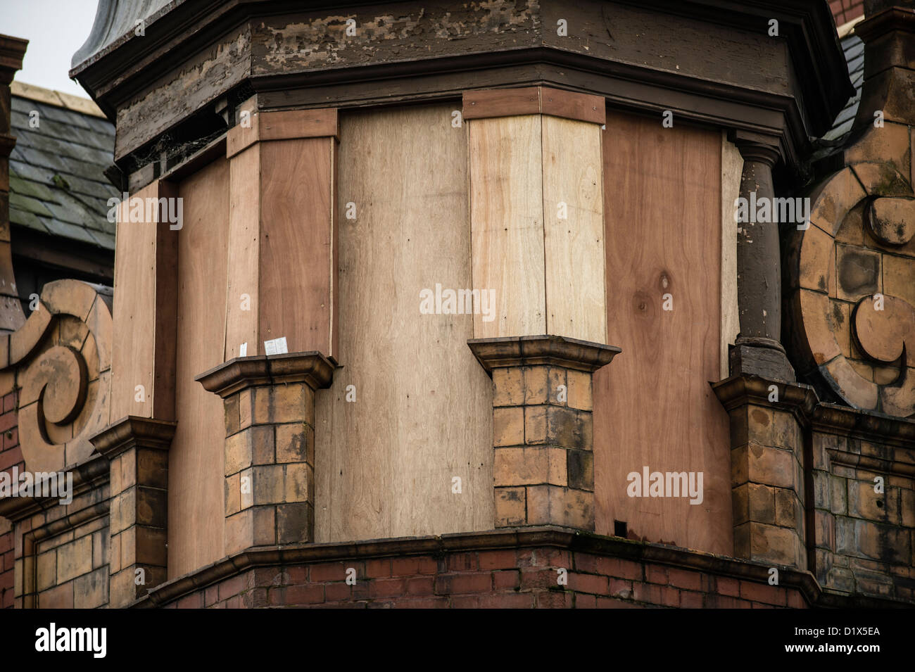 The boarded up corner turret windows of a Victorian era building in need of repair and renovation, UK - Stock Image
