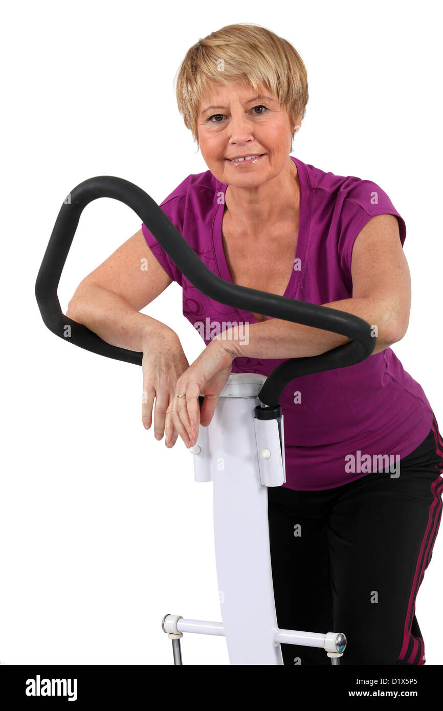 senior woman doing exercises in the gym - Stock Image