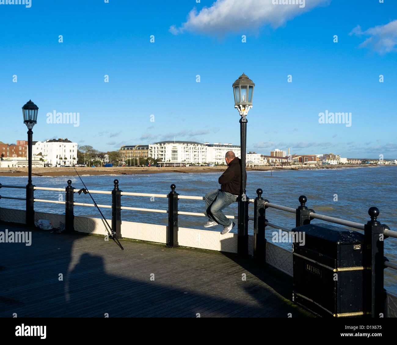 A man sits on the railings of Worthing pier whilst he fishes - Stock Image