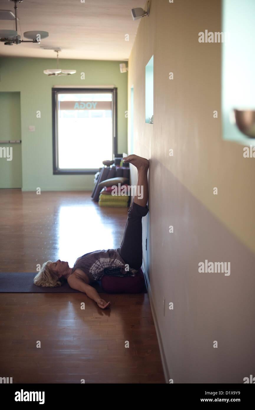 Interior of yoga studio with woman using bolster pillows. - Stock Image
