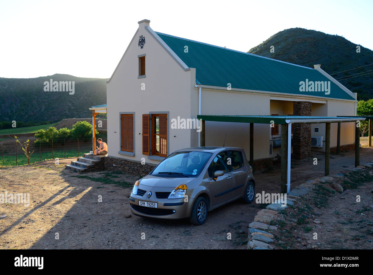 Cream cottage with green roof, car in foreground, mountains at sunset in the Klein Karoo, South Africa - Stock Image